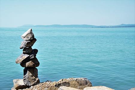 balanced of gray stone near body of water