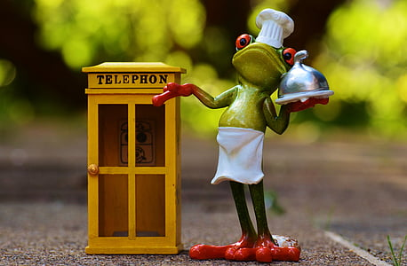 selective focus photography of frog waiter beside telephone booth miniature