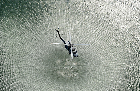 black helicopter forming water ripple