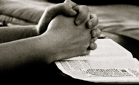 person praying hands on boook