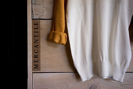 white and brown Mercantile sweatshirt on brown board