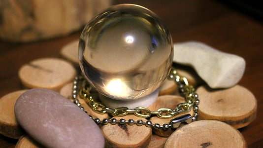 selective focus photography of crystal ball on round brown surface