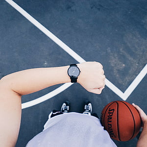 person looking at black analog watch holding Spalding basketball