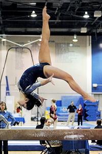 gymnast back flipping on beam