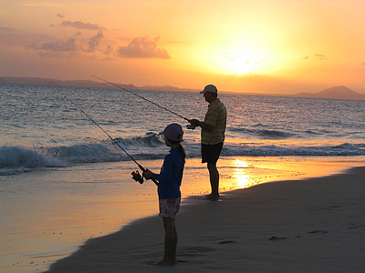 boy and man fishing on the seashore