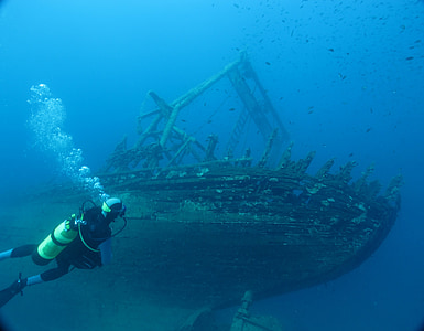 man diving underwater with brown wooden ship