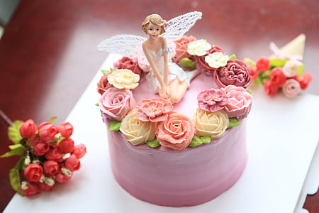 pink icing covered cake on table with fairy figurine