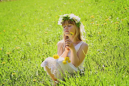 girl wearing floral sleeveless dress with flower crown sitting on green grass field during daytime