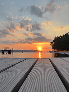dock above body of water under white clouds during golden hour