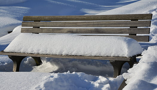 snow on brown wooden bench