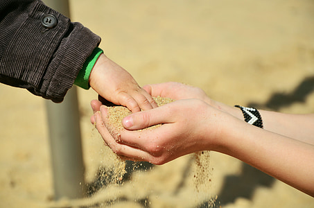 child's hand on other person's hands with sand at daytime