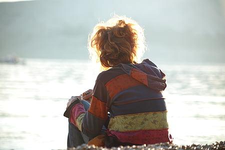 girl sitting beside body of water