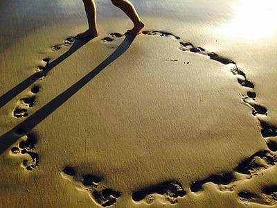 person walking on beach sand