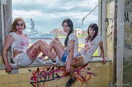 three women in white top sitting on window