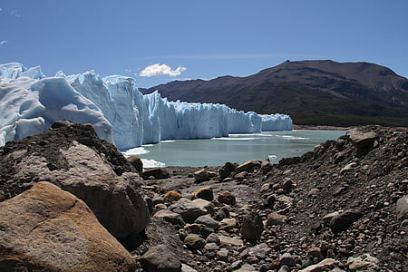 iceberg beside body of water and mountains during daytime