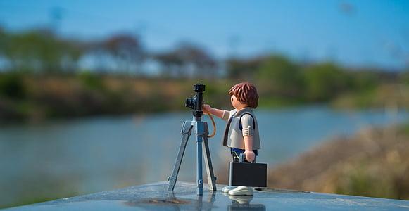 man holding camera figurine on black surface