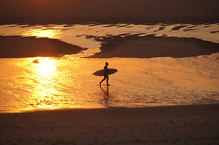 man holding surfboard near seashore during dawn