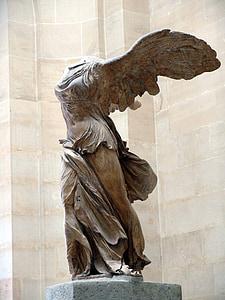 angel statue near white wall