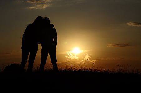 silhouette of two people on grass