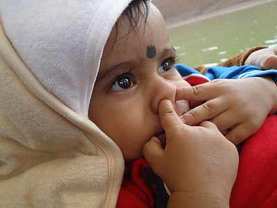 baby with fingers on nose wearing red top