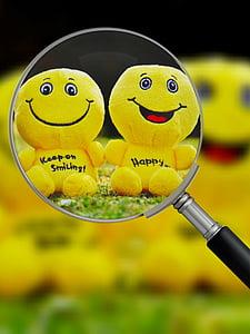 two yellow emoji plush toys in magnifying glass