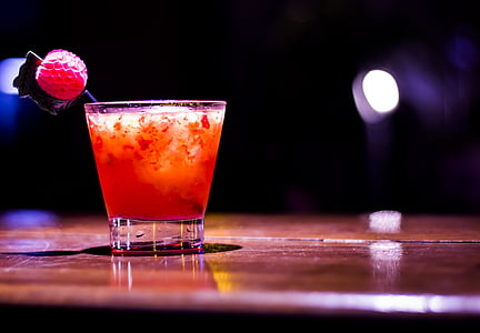 closeup photo of shot glass with orange liquid