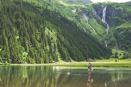 man fishing on lake near green forest