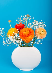 orange, yellow, and red petaled flowers in white ceramic vase