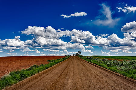 brown rocky road under blue and white cloudy sky