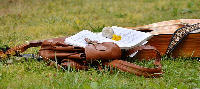 brown acoustic guitar beside brown leather bag on grass field