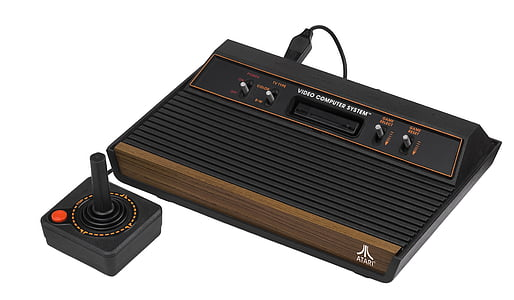 brown and black Atari with joystick