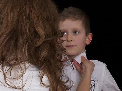 boy wearing white collared shirt standing near woman wearing white shirt