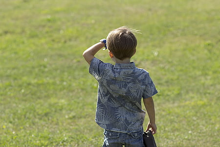 boy wearing gray and white floral short-sleeved shirt facing grass field