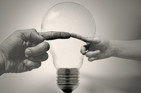 grayscale photo of human finger with light bulb