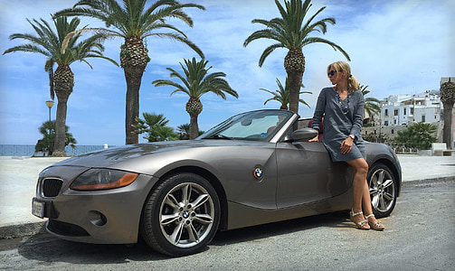 woman in gray long-sleeved dress beside gray BMW convertible coupe during daytime