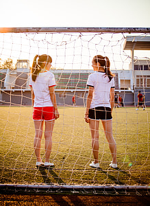two women standing in front of soccer goal