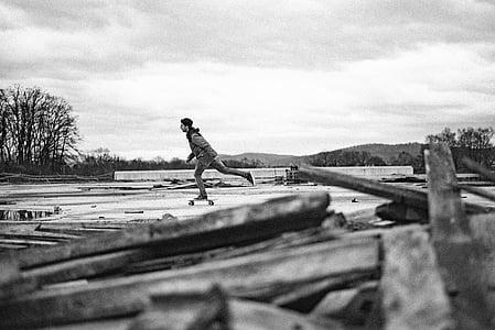 grayscale photo of man playing skateboard