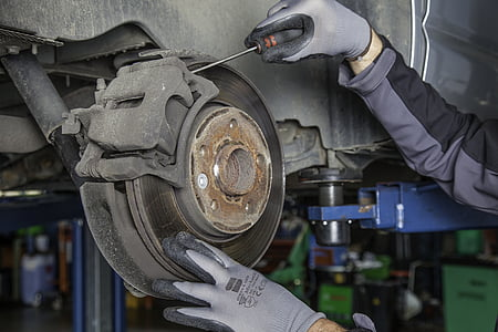 person fixing a car brake set