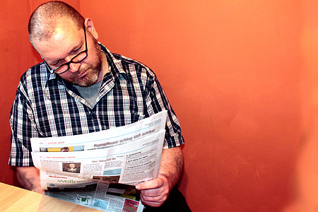 man wearing black and white plaid button-up sport shirt while reading newspaper