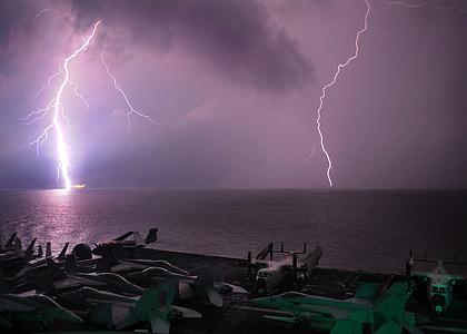 warm wave ocean under lightning at nighttime