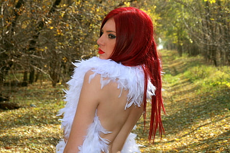 red haired woman in white dress standing in forert