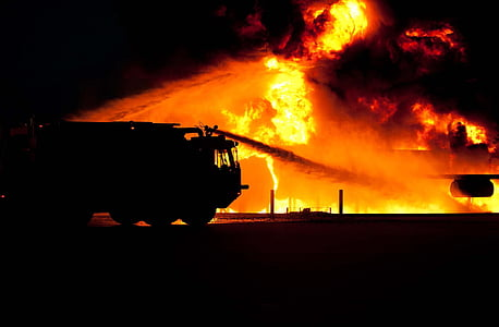 silhouette photo of fire truck trying to put the fire out