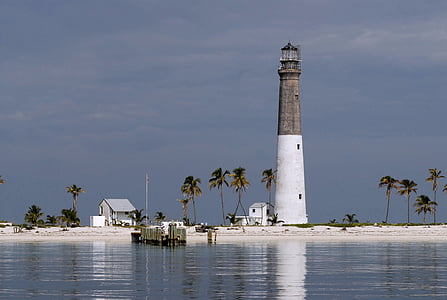 landscape photo of beach with white and gray lighthouse