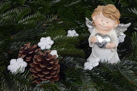 cherub holding heart near pine cone photograph