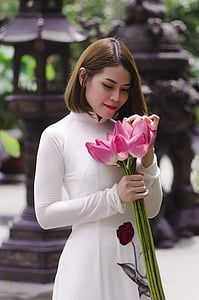 woman holding pink petaled flowers