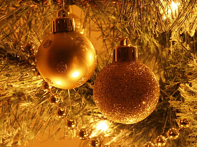 two gold baubles hanging on Christmas tree