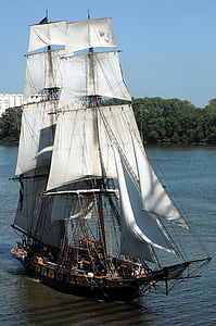 white sailing ship surrounded with green trees