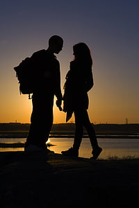 man and woman standing in front of each other near body of water in silhouette photography during golden hour