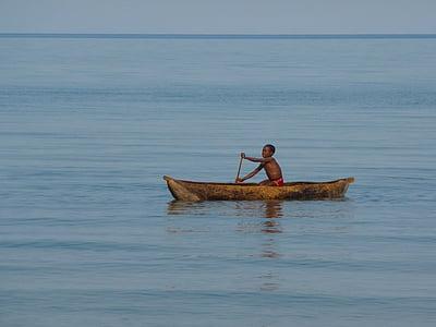 boy rowing in brown canoe