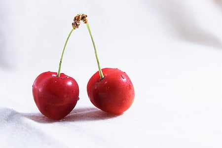two red cherries on white surface